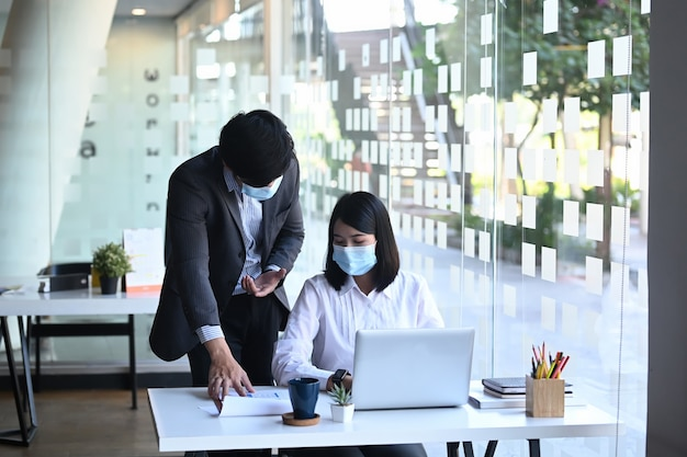 Business meeting of two partners wearing protective mask working together and discussing strategy for company growth in office.