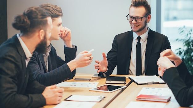 Деловая встреча. молодой мужской менеджер проекта дает инструкции профессиональной команде.
