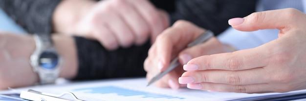 비즈니스 남성과 여성 문서 근접 촬영에서 차트를 논의.