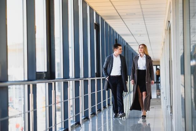 モダンなビジネスセンターの大きなパノラマの窓の背景に笑顔で握手するビジネスの男性と女性。ダークなビジネススーツを着たモデル。