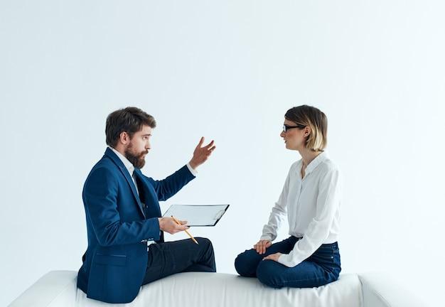 ビジネスの男性と女性がソファに座って従業員の心理的な仕事を伝えます