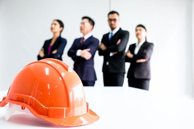 Бизнесмены и женщины стоя за оранжевой шляпой.