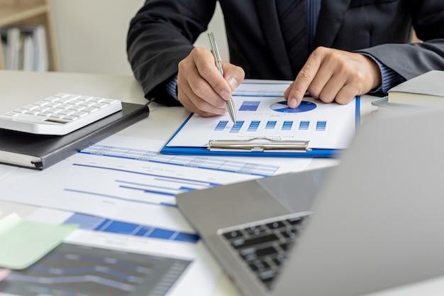 Деловые люди изучают финансовые документы компании, чтобы проанализировать проблемы и найти решения, прежде чем передать информацию на встречу с партнером. финансовая концепция.
