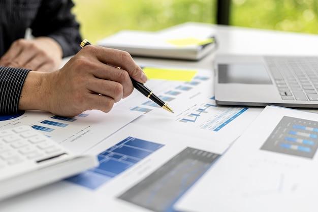 비즈니스맨은 파트너와의 회의에 정보를 가져오기 전에 문제를 분석하고 솔루션을 찾기 위해 회사의 재무 문서를 보고 있습니다. 금융 개념입니다.