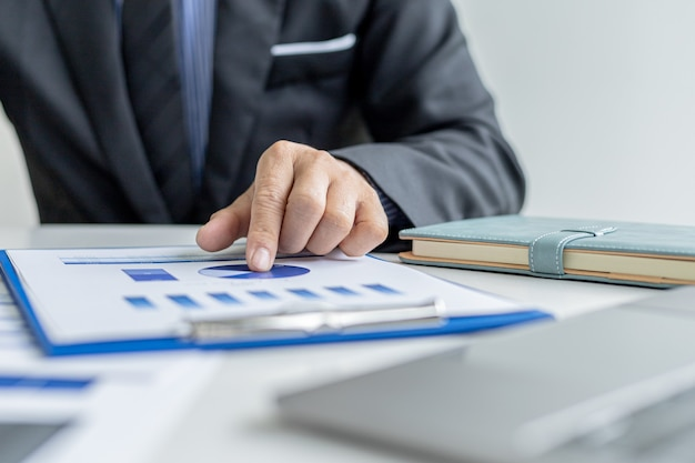 Business men are looking at the company's financial documents to analyze problems and find solutions before bringing the information to a meeting with a partner. financial concept.