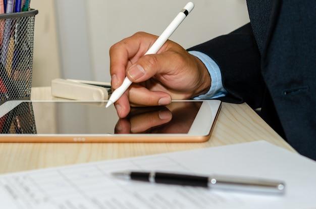 ビジネスマンは、デスクでビジネス文書とペンを備えたタブレットを使用しています。在宅勤務