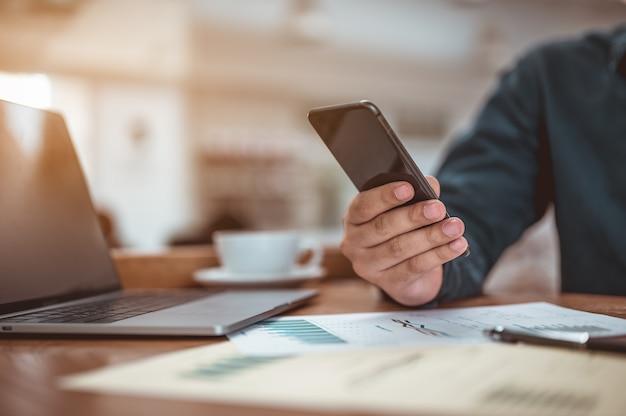ビジネスマンは昼食時に携帯電話を使ってソーシャルメディアをチェックしていますビジネスと仕事