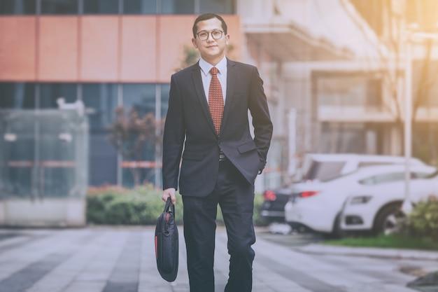 ビジネスマンは、駐車場でラップトップを運ぶ