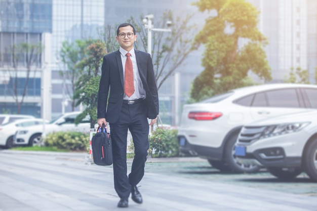 Business men carry laptops in the parking lot