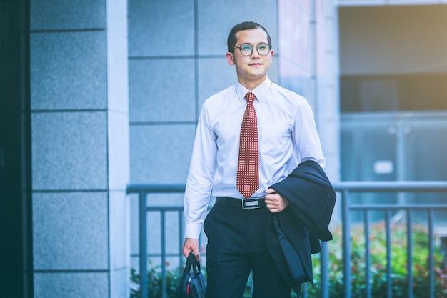 ビジネスマンはオフィスビルの入り口で仕事をするためにノートパソコンを持ち歩く