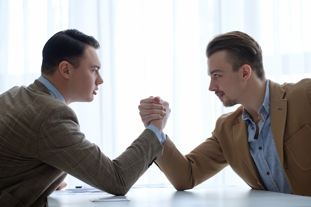 ビジネスマンは対決し、反対します。リーダーシップを決定するためのアームレスリング。