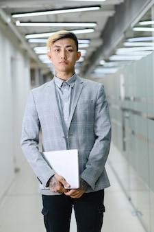 사무실에서 아시아에서 비즈니스 남자 젊은 아시아 관리자는 사무실에 서 그의 손에 고품질의 노트북을 보유하고 photo