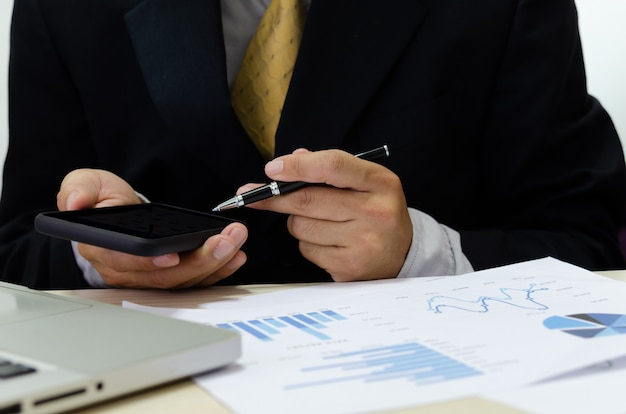 Business men hand holding cell phones and pens on the desk have business documents graphs financial reports