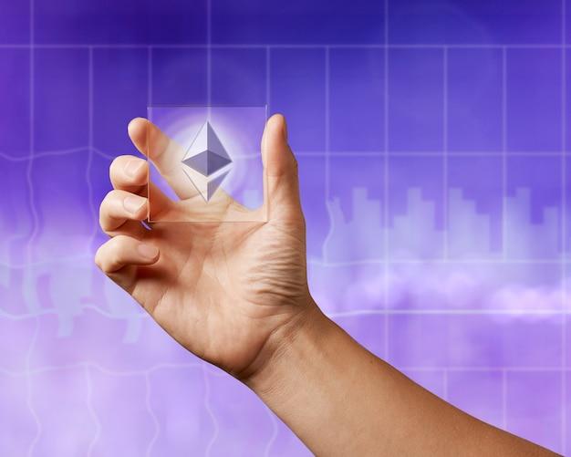 Деловые люди держат прозрачный экран с иконой этереума на ультрафиолетовом фоне города. бизнес, технология блокчейн.