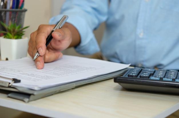 비즈니스 남자는 비즈니스 문서를보고 책상에서 펜을 잡습니다. 재택 근무