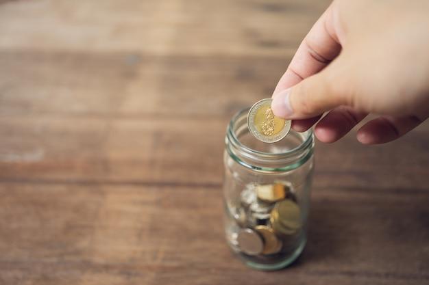 ビジネスの男性コインをガラスの瓶に入れる