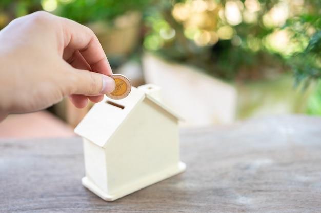 ビジネスの男性家のスタイルの貯金箱にコインを入れますお金を節約するには、お金を節約