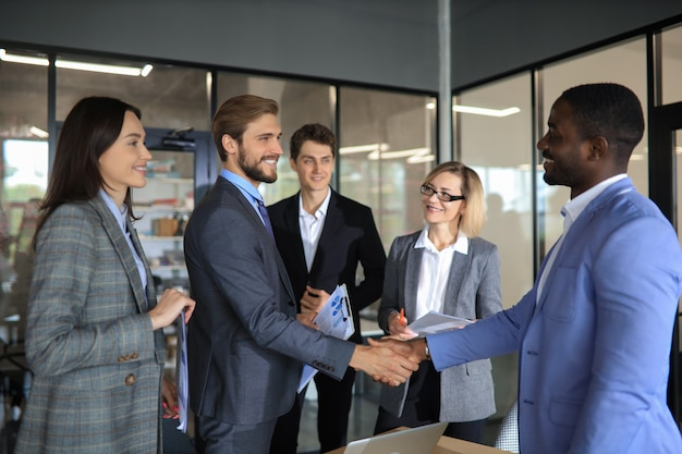 Business men shaking hands while their colleagues applauding and smiling in the background.