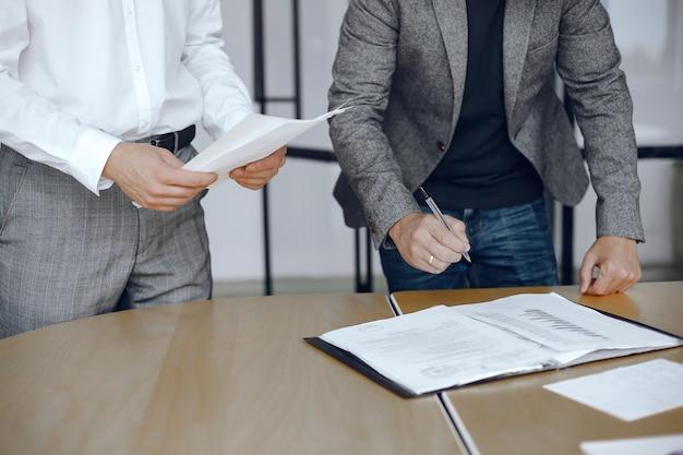 변호사의 책상에 앉아 비즈니스 남자. 중요한 문서에 서명하는 사람들.