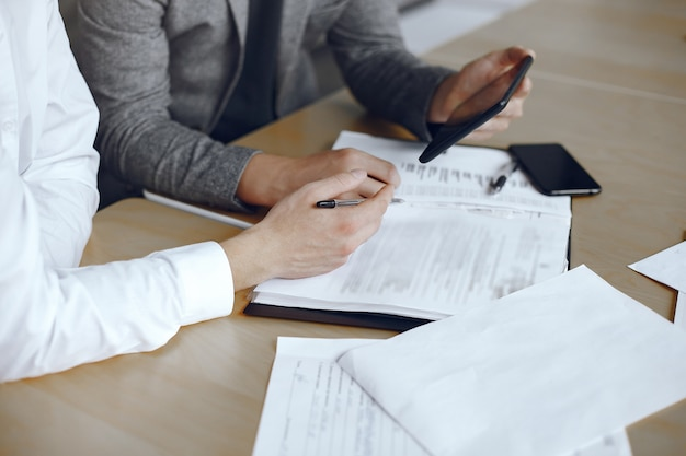 Деловые люди сидят за столом адвоката. люди подписывают важные документы.