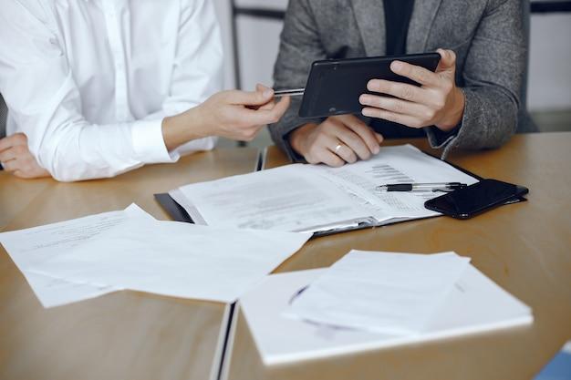 弁護士の机に座っているビジネスマン。重要な文書に署名する人々。