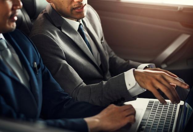 Business men use laptop car