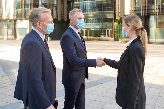 Business men and woman in face masks and office suits meeting in city, shaking hands near building. side view shot. communication and virus protection concept