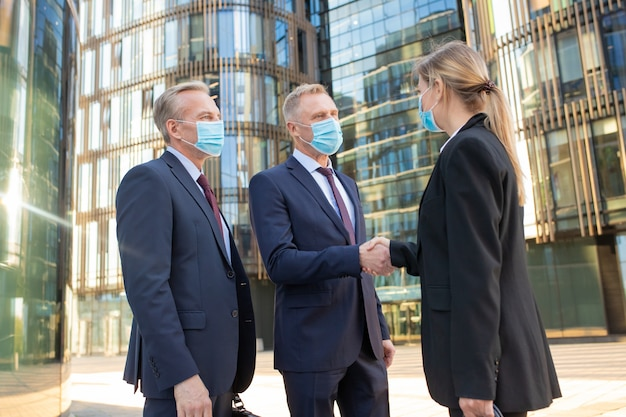 Business men and woman in face masks shaking hands near office buildings, meeting and talking in city. side view, low angle. cooperation and coronavirus concept