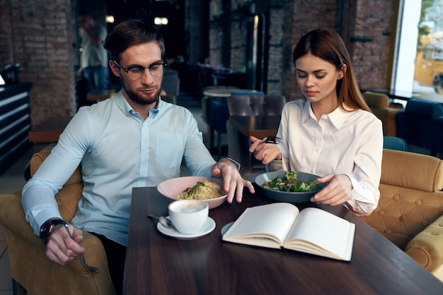 Business men and women sit at the table with the phone chatting breakfast