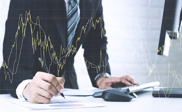 Business men work on the table analyze graphs financial report in documents and computers.
