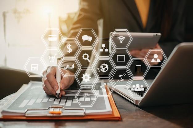 Деловые люди, работающие с планшетом, деловым документом и ноутбуком портативного компьютера в домашнем офисе.