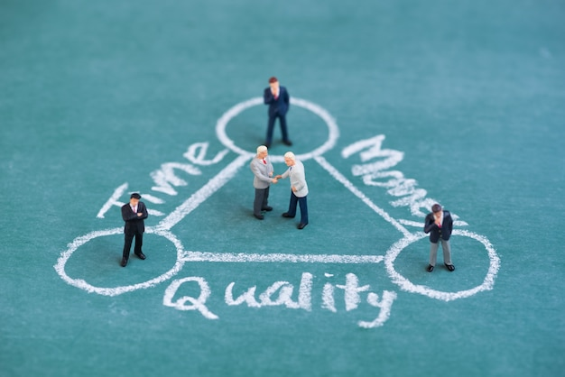 Business miniature people shaking hand in balance time , quality and money diagram