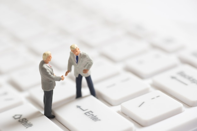 Business miniature people shaking hands on enter button of keyboard