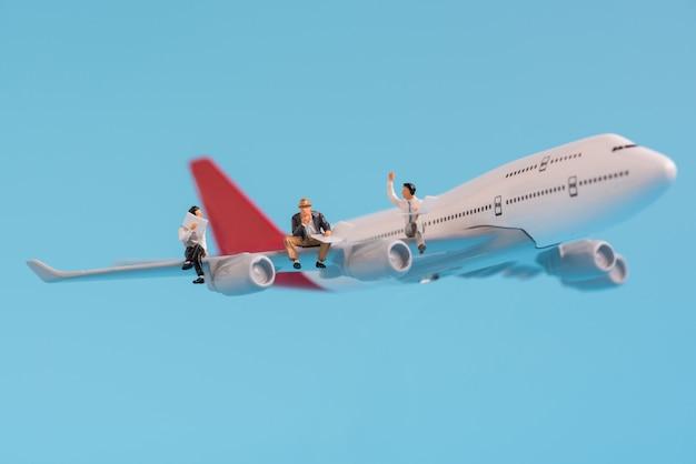 Business miniature people sitting on airplane