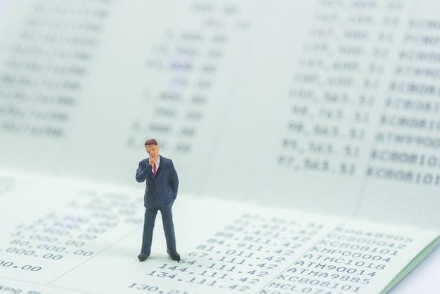Business miniature standing on book bank background