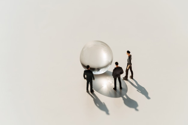 Business miniature toy with globe glass on white background