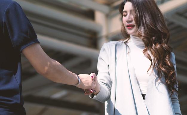비즈니스 현대 여성은 파트너와 악수하고 협업 거래 후 만족스럽게 미소를 짓습니다.