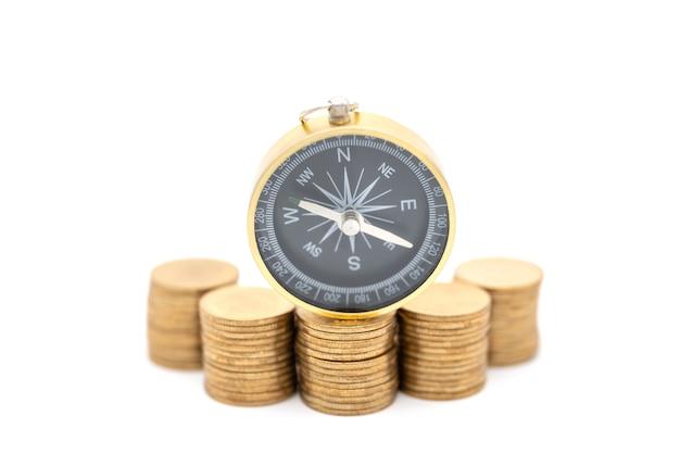 비즈니스, 돈 방향 및 계획 개념입니다. 흰색 배경 가진 금화 더미에 빈티지 나침반의 근접 촬영.