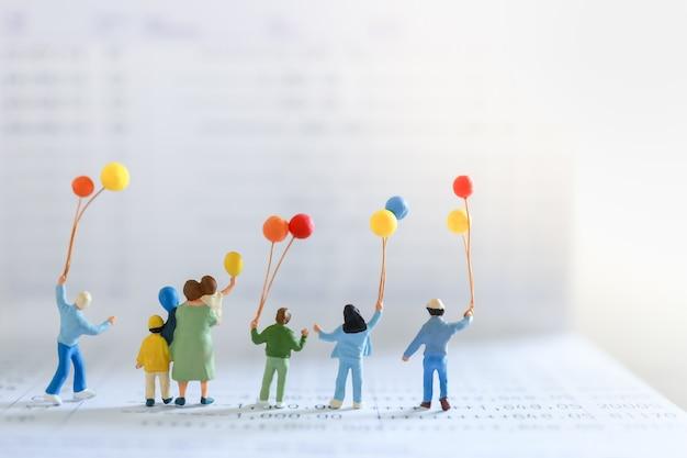 비즈니스, 돈, 금융 및 가족 개념. 복사 공간 은행 통장에 다채로운 풍선 서 어린이와 아이 미니어처 그림 사람들의 그룹입니다.