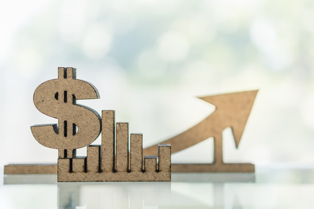 Business, money, finance growth and planning concept. close up of wooden dollar sign and bar chart graph and arrow with copy space.