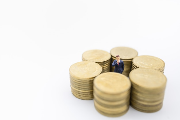 Business, money, finance and management . close up of businessman miniature figure standing center of row of stack of gold coins.