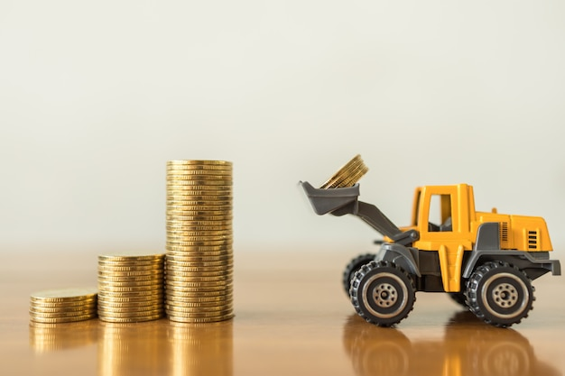 Business, money,  finance and saving  concept. close up of miniature mini loader truck contain 4 coins and puting to top of stack of gold coins on wooden table with copy space.