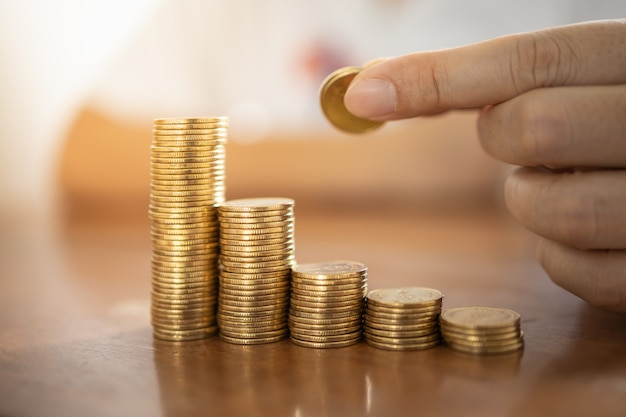 Business, money, finance, secure and saving concept. close up of man hand holding and put coin to stack of gold coins on wooden table.