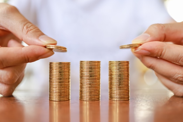 Business, money, finance, secure and saving concept. close up of two man hand holding and put coins to top of stack of gold coins on wooden table.