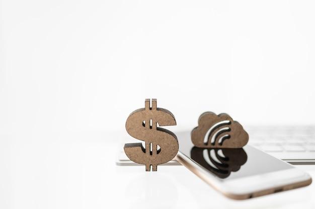 비즈니스, 돈, 금융 및 기술 개념입니다. 모바일 스마트폰 및 복사 공간이 있는 컴퓨터 키보드에 구름과 신호 아이콘이 있는 목조 미국 달러 기호를 닫습니다.