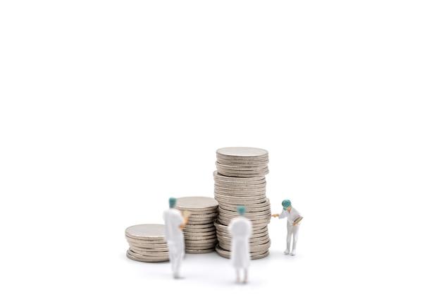 비즈니스, 돈 의료 개념입니다. 흰색 바탕에 동전 더미가 서 있는 환자 파일과 함께 모자와 얼굴 마스크를 쓴 의사 미니어처 그림 사람들.