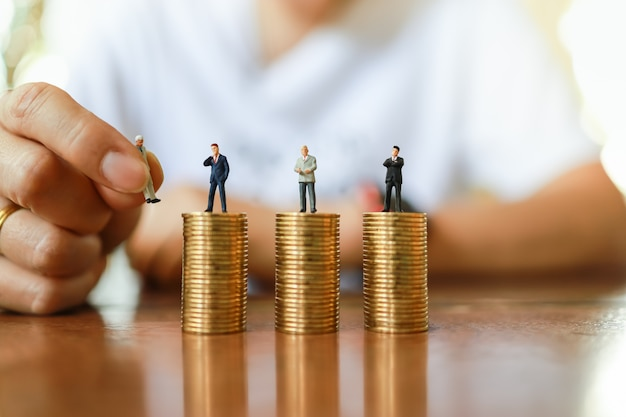 Business, money and human management resource concept. close up of man hand holding businessman miniature figure people and putting to change figure on top od stack of gold coin on wooden table.