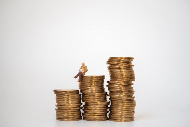 Бизнес, денежные вложения и концепция планирования. бизнесмен миниатюрная фигура люди рисуют сидя и читая газету на стопке золотых монет на белом фоне.
