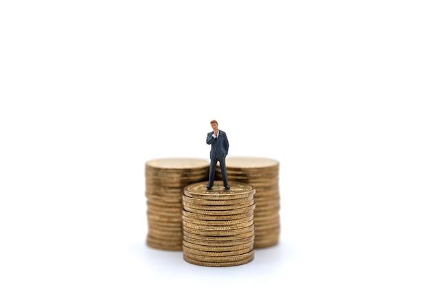 비즈니스, 돈 투자 및 계획 개념입니다. 사업가 미니어처 그림 사람들은 흰색 바탕에 금화 더미에 서 있는 그림.