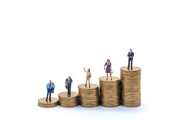 비즈니스, 돈 투자 및 계획 개념입니다. 사업가 및 사업가 미니어처 그림 사람들의 그룹은 흰색 바탕에 금화 더미에 서 있는 모습입니다.